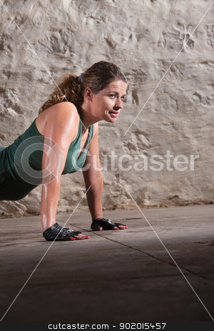 Young Lady Doing Push-ups stock photo, Young beautiful lady doing push ups indoors by Scott Griessel