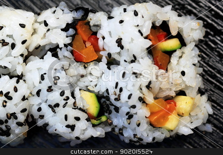 Sushi stock photo, Close up of a sushi California roll on a black board. by Henrik Lehnerer
