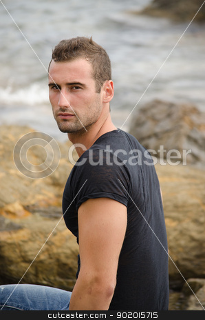 Handsome male model sitting on rock by the sea stock photo, Handsome and fit male model sitting on rock by the sea by Stefano Cavoretto