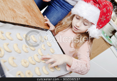 christmas baking stock photo, little girl in santas hat baking christmas sweets by photomim
