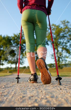 Nordic walking in summer stock photo, Closeup of woman's legs with nordic walking poles by kamsta