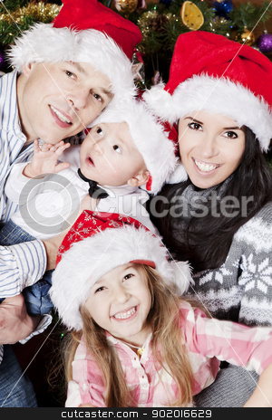 a happy family stock photo, happy and smiling family in santas hats by photomim