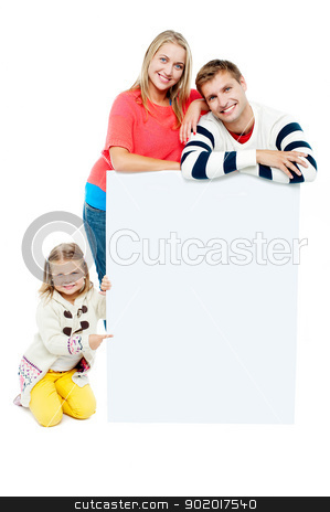 Portrait of happy family presenting blank whiteboard stock photo, Portrait of happy family presenting blank whiteboard. Studio shot by Ishay Botbol