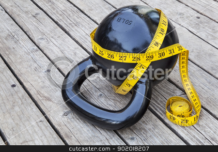 kettlebell and measuring tape stock photo, kettlebell and measuring tape on wooden deck - fitness and exercise concept by Marek Uliasz