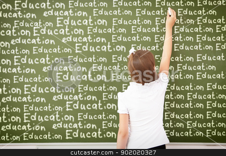 Scoolgirl standing near blackboard stock photo, Scoolgirl standing in class near a green blackboard by Sergey Nivens