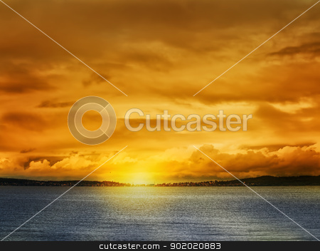 sunset at the lake stock photo, Bright sunset at the lake with town at horizon  by Sergej Razvodovskij