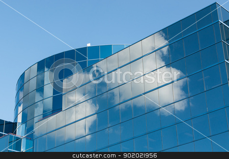 Modern Office Building Reflecting the Clouds stock photo, A modern reflective office building reflects the white clouds in a blue sky. by Brian Guest