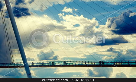 Modern bridge design stock photo, Modern bridge against the cloudy sky and people silhouettes by carloscastilla