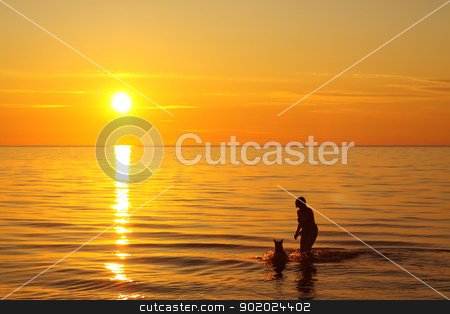 Ladoga lake stock photo, Woman and dog bathing in the lake at dawn time by Yulia Chupina