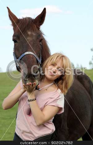 Portrait of a girl and horse stock photo, Portrait of a girl and a dark brown horse.  by Yulia Chupina