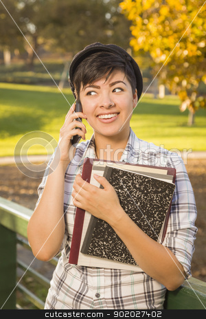 Mixed Race Female Student Holding Books and Talking on Phone stock photo, Outdoor Portrait of a Pretty Mixed Race Female Student Holding Books and Talking on Her Cell Phone on a Sunny Afternoon. by Andy Dean