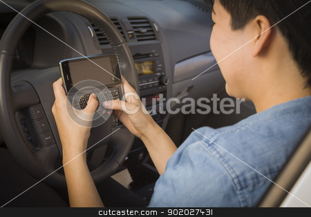 Mixed Race Woman Texting and Driving stock photo, Mixed Race Woman with Smart Phone Texting and Driving. by Andy Dean