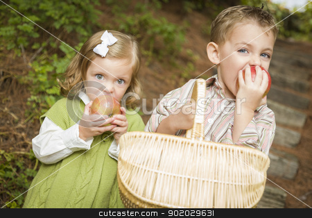 Adorable Children Eating Red Apples Outside stock photo, Two Adorable Children Eating Delicious Red Apples Outside. by Andy Dean
