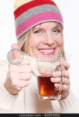Mid age Woman With Hot tea showing thumbs up stock photo, Mid age Woman With Hot tea Wearing Winter Clothes showing thumbs up on a white background by yekostock