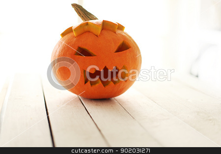 Halloween pumpkin stock photo, Halloween pumpkin on a white wooden surface by yekostock