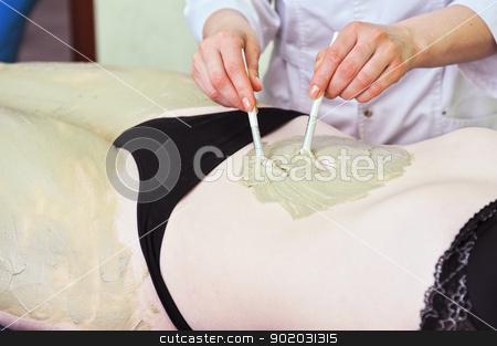 body mask stock photo, Woman having clay body mask apply by beautician by olinchuk