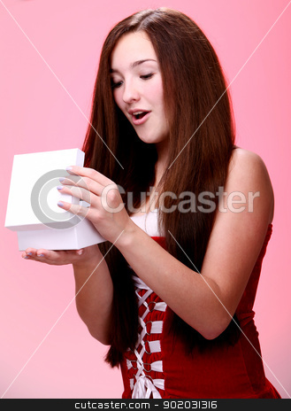 Beautiful christmas girl in red opening a gift stock photo, Portrait of young and beautiful christmas girl in red opening a gift by yekostock