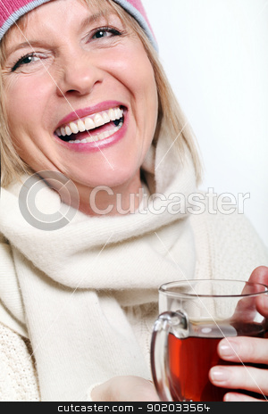 Mid age Woman With Hot tea Wearing Winter Clothes stock photo, Mid age Woman With Hot tea Wearing Winter Clothes on a white background by yekostock