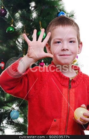 christmas portrait stock photo, Young boy showing five fingers in front of christmas tree, looking at camera, vertical shot by Milsi Art