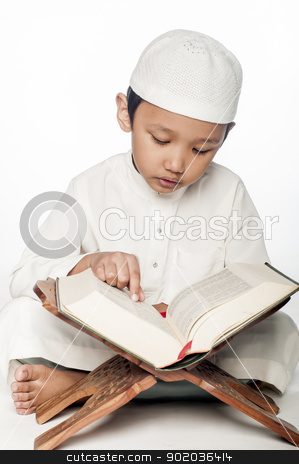 Reading the Quran stock photo, A little muslim boy wearing islamic attire reading the holy Quran by Hasnuddin Abu Samah