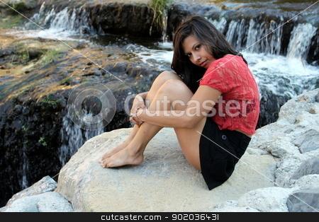 Hispanic Woman Creek stock photo, Hispanic woman sitting at water edge of a creek. by Henrik Lehnerer