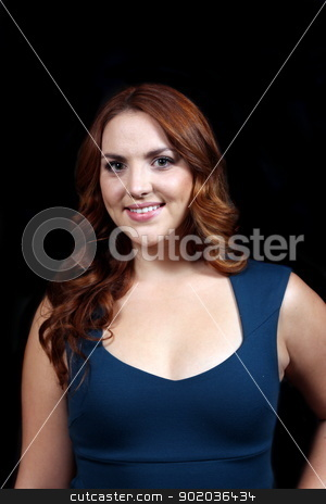 Woman Red Hair stock photo, Red hair woman with blue dress in front of dark background. by Henrik Lehnerer