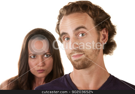 Sneaky Man with Skeptical Girlfriend stock photo, Sneaking male with suspicious woman behind him by Scott Griessel