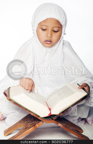 Girl Reading the Quran stock photo, A muslim girl wearing praying attire reading the holy quran by Hasnuddin Abu Samah
