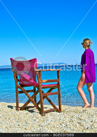 young sexy woman in purple sun dress on a beach