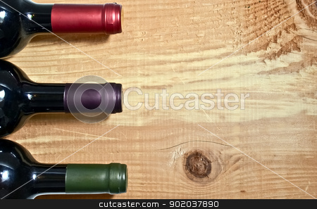 Wine bottle on a wooden table stock photo, Wine bottle on a wooden table by vician