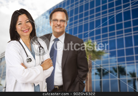 Hispanic Doctor or Nurse and Businessman in Front of Building stock photo, Attractive Hispanic Doctor or Nurse and Businessman in Front of Corporate Building. by Andy Dean