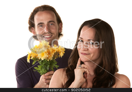 Young Couple Expressing Forgiveness stock photo, Grinning woman and smiling man holding flowers by Scott Griessel