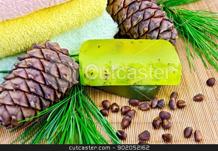Soap homemade green with cedar cones stock photo, Two green homemade soap, the cedar cone with a branch, nuts cedar, three towels on a bamboo mat by rezkrr