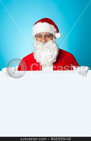Aged Santa standing behind a blank ad board stock photo, Aged Santa standing behind a blank ad board, marketing concept. by Ishay Botbol