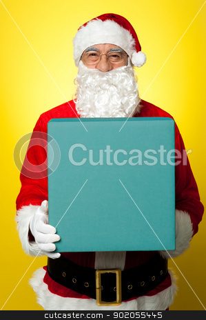 Isolated smiling Santa holding gift box stock photo, Isolated smiling Santa holding gift box and looking at camera. by Ishay Botbol