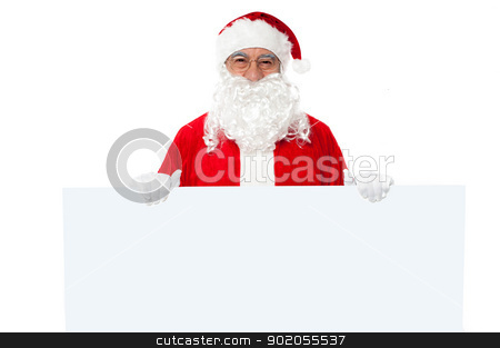 Advertise your business here stock photo, Joyful Santa standing behind a blank ad board. Advertise your business. by Ishay Botbol