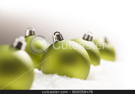 Green Christmas Ornaments on Snow Over a Grey Background stock photo, Green Christmas Ornaments on Snow Flakes Over a Grey Background, White at the Top and Right - Great for a Corner Image. by Andy Dean