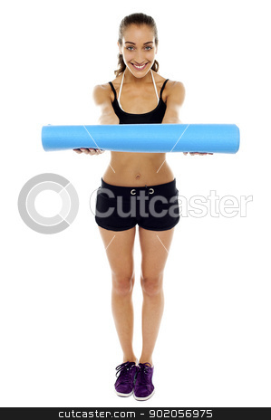 Woman holding a blue mat in her outstretched arms stock photo, Attractive woman in gym attire  holding a blue mat in her outstretched arms by Ishay Botbol