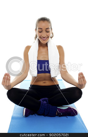 Attractive brunette meditating in lotus posture stock photo, Attractive brunette meditating in lotus posture, sitting on blue mat. by Ishay Botbol