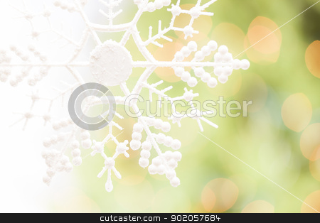 Snowflake Over an Abstract Green and Gold Background stock photo, White Glittery Snowflake Over an Abstract Green and Gold Background. by Andy Dean