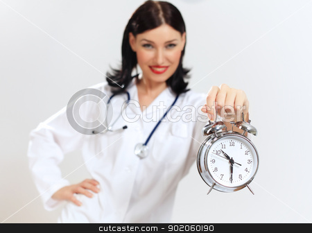 Young female doctor with clocks stock photo, Portrait of happy successful young female doctor holding clocks by Sergey Nivens
