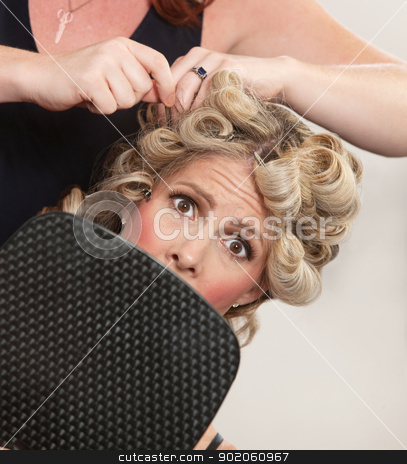 Nervous Customer in Hair Salon stock photo, Nervous female holding mirror with hair stylist working by Scott Griessel