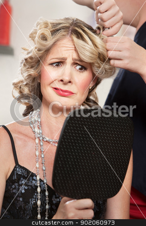 Dissatisfied Hair Salon Client stock photo, Dissatisfied pretty woman in salon holding mirror by Scott Griessel
