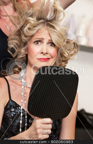 Woman Worried About Hairdo stock photo, Worried lady holding mirror with stylist working on hair by Scott Griessel