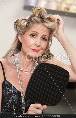 Lady Trying to Fix Her Hair stock photo, Frustrated middle aged European beauty trying to fix her hair by Scott Griessel