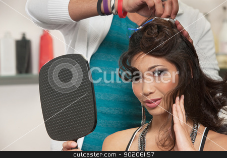 Woman Watching Hair Stylist Work stock photo, Sexy woman feeling hair and holding mirror as stylist works by Scott Griessel