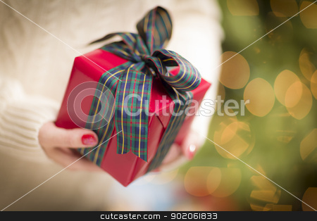 Woman Wearing Seasonal Red Mittens Holding Christmas Gift stock photo, Woman Wearing A Sweater and Seasonal Red Mittens Against an Abstract Green and Golden Background Holding A Beautifully Wrapped Christmas Gift with Narrow Depth of Field. by Andy Dean
