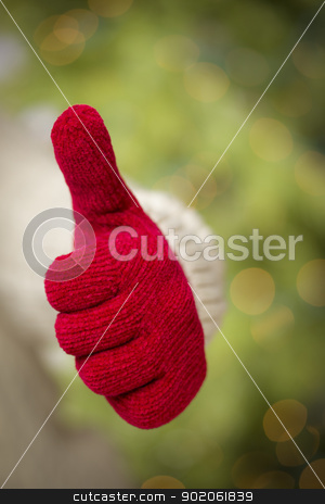 Woman Wearing Red Mittens Holding Out Thumbs Up Hand Sign stock photo, Woman in Sweater with Seasonal Red Mittens Holding Out a Thumb Up Sign with Her Hand. by Andy Dean