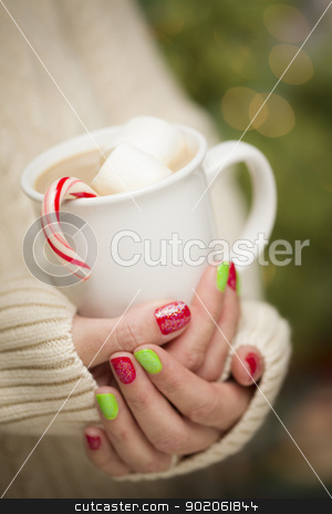 Woman with Red and Green Nail Polish Holding Cup of stock photo, Woman in Sweater with Seasonal Red and Green Nail Polish Holding a Warm Cup of Hot Cocoa. by Andy Dean