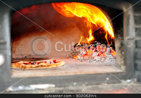 Wood Fired Pizza Oven stock photo, Baking Pizzas in a wood burning pizza oven with glowing coals and embers with flames  shooting up by Lynn Bendickson